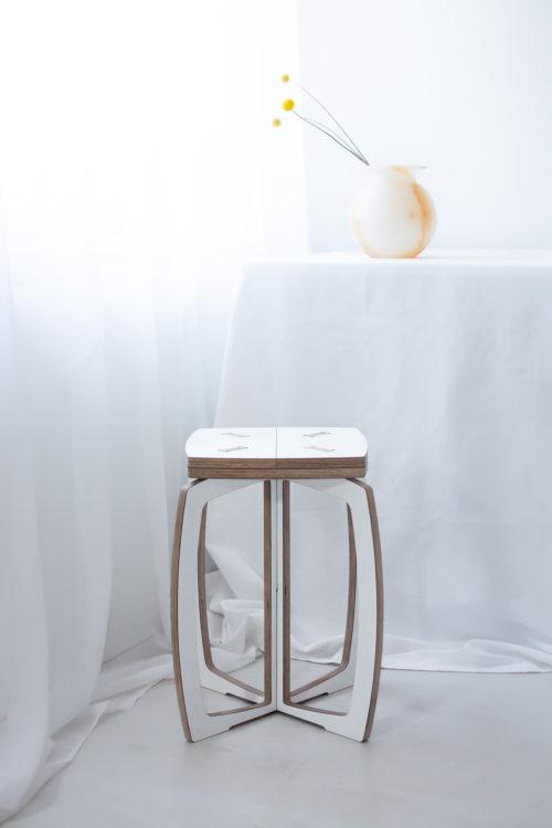 Opilion valkoinen design jakkara. Taustalla on valko-oranssi ruukku jossa kolme oranssia kukkaa.